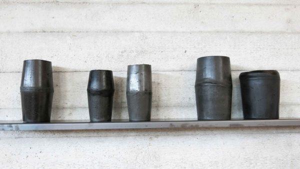 Cristina Treppo, Disperdere e contenere, 2019, 100 vasi in resina-cemento, cera, piani di ferro di 2x13x150 cm ciascuno, dimensioni site-specific